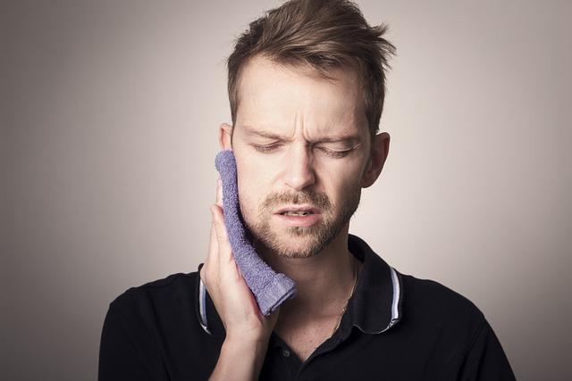 tandvärk, kille håller handduk mot kinden